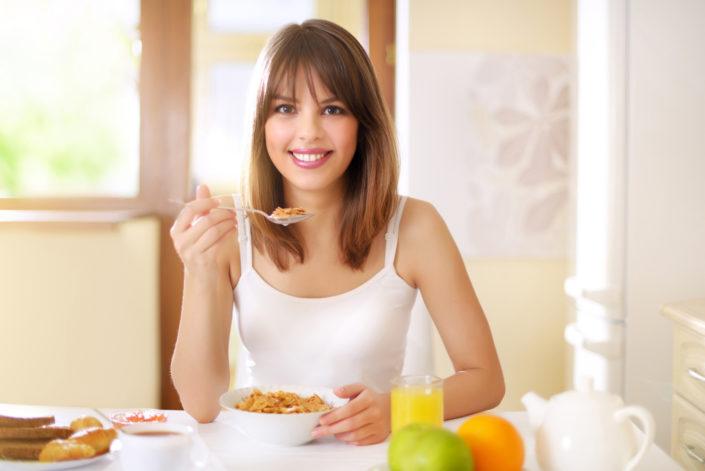 Glückliche Frau isst Müsli